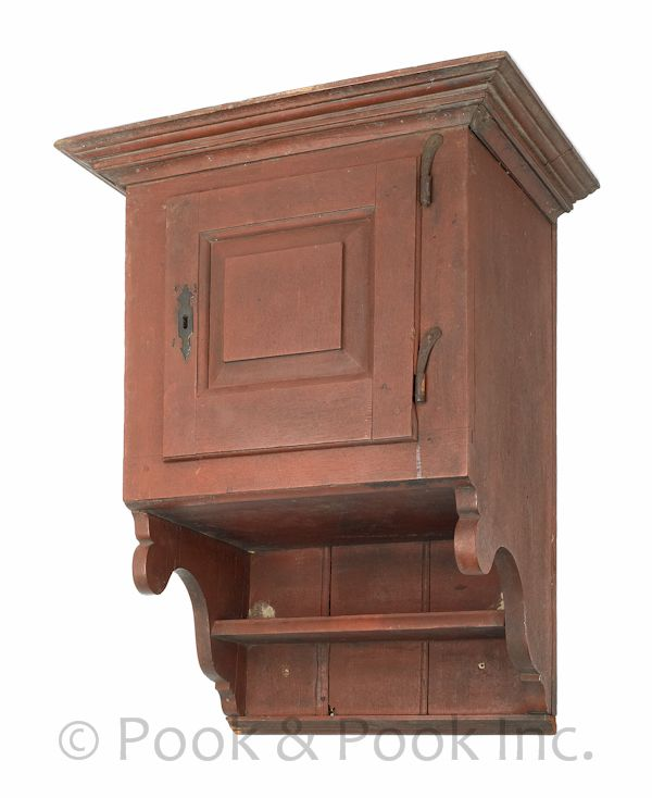 Pennsylvania walnut hanging cupboard, circa 1770, the molded cornice overhanging a raised panel door, with an open shelf with scrolled sides, retaining an old open shelf with scrolled sides, old red painted surface, 26 H. x 17.25 W. x 12.5 D.