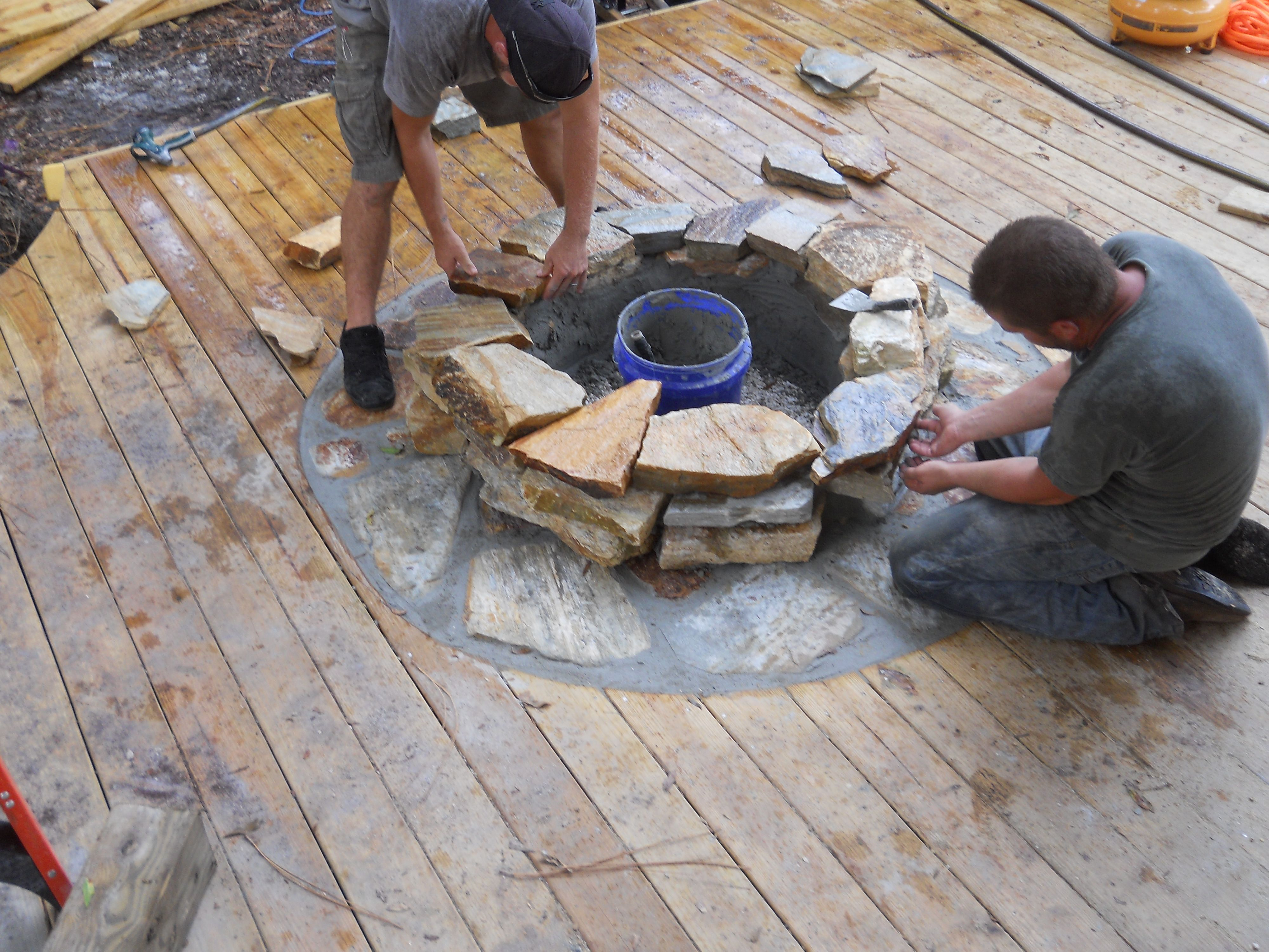 craftsmen constructing a natural stone fire pit on wooden deck with