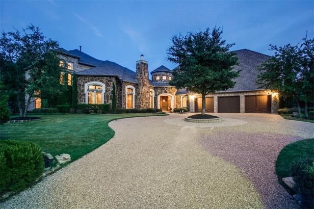 Rich stone combines with a circle driveway & mature landscaping for striking curb appeal