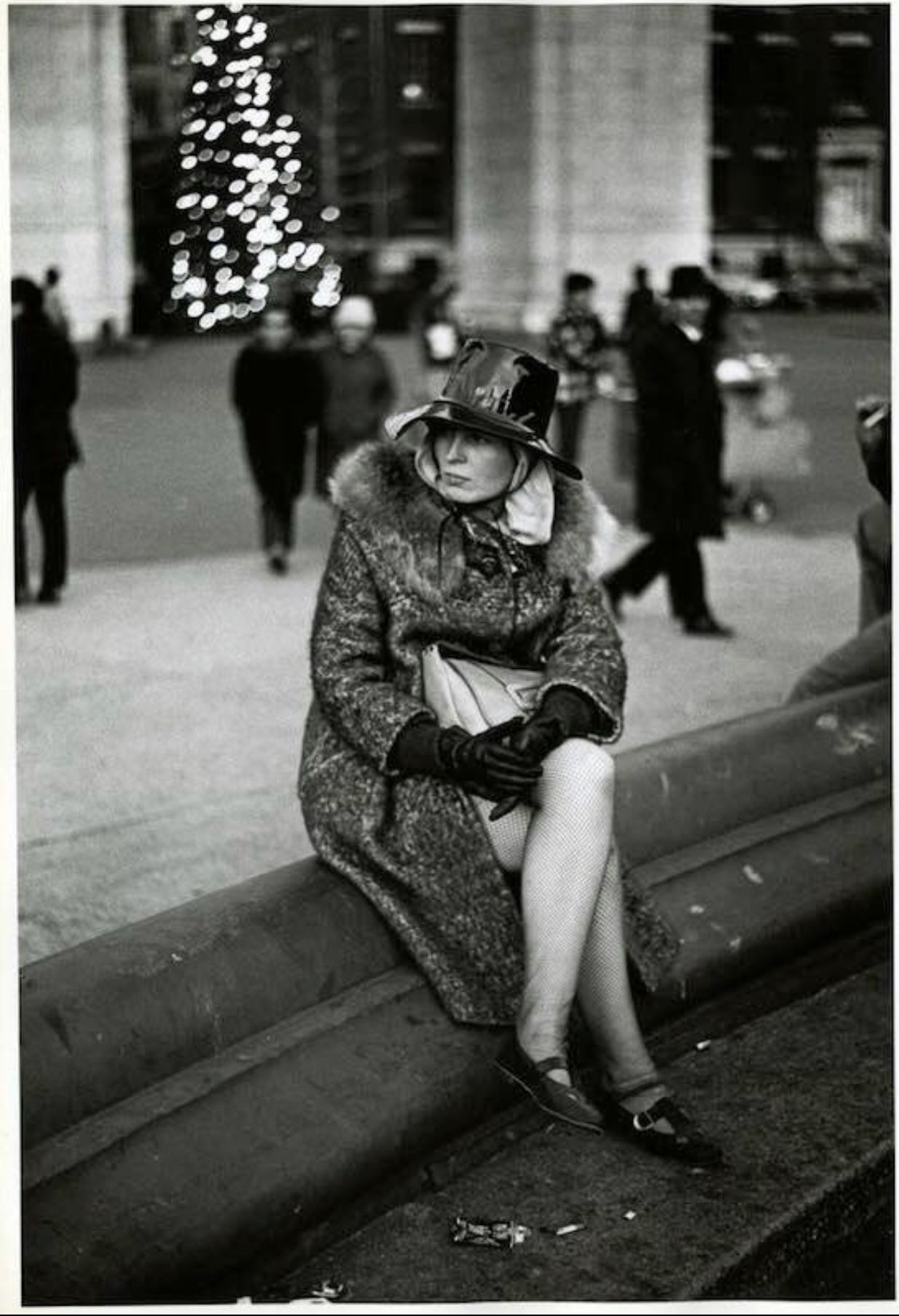 1968 woman sitting in washington square park ledge of fountain with the parks christmas