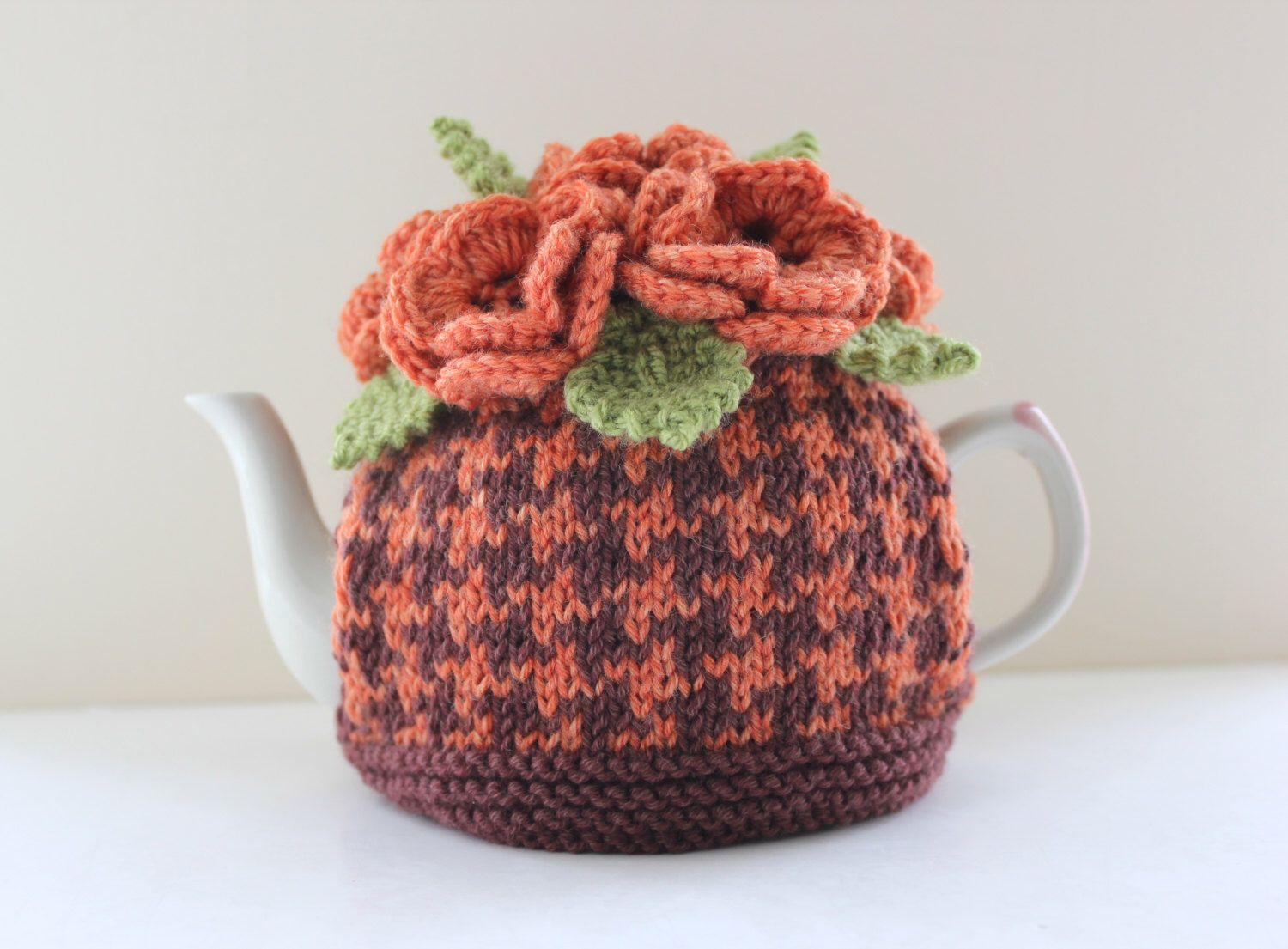 Hand-knitted Floral 'Spiced Pumpkin' Houndstooth tea cosy in cashmerino. https://www.etsy.com/uk/listing/229617970/hand-knitted-floral-spiced-pumpkin