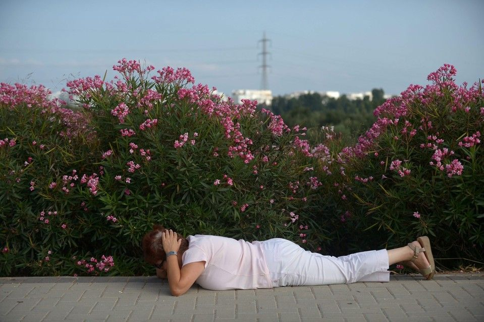 Week of Jul 5-11, 2014 An Israeli woman takes cover while sirens sound in the city of Ashdod, Israel. Israel launched a military operation in response to a renewed wave of rockets out of the Gaza Strip. Avi Roccah/European Pressphoto Agency