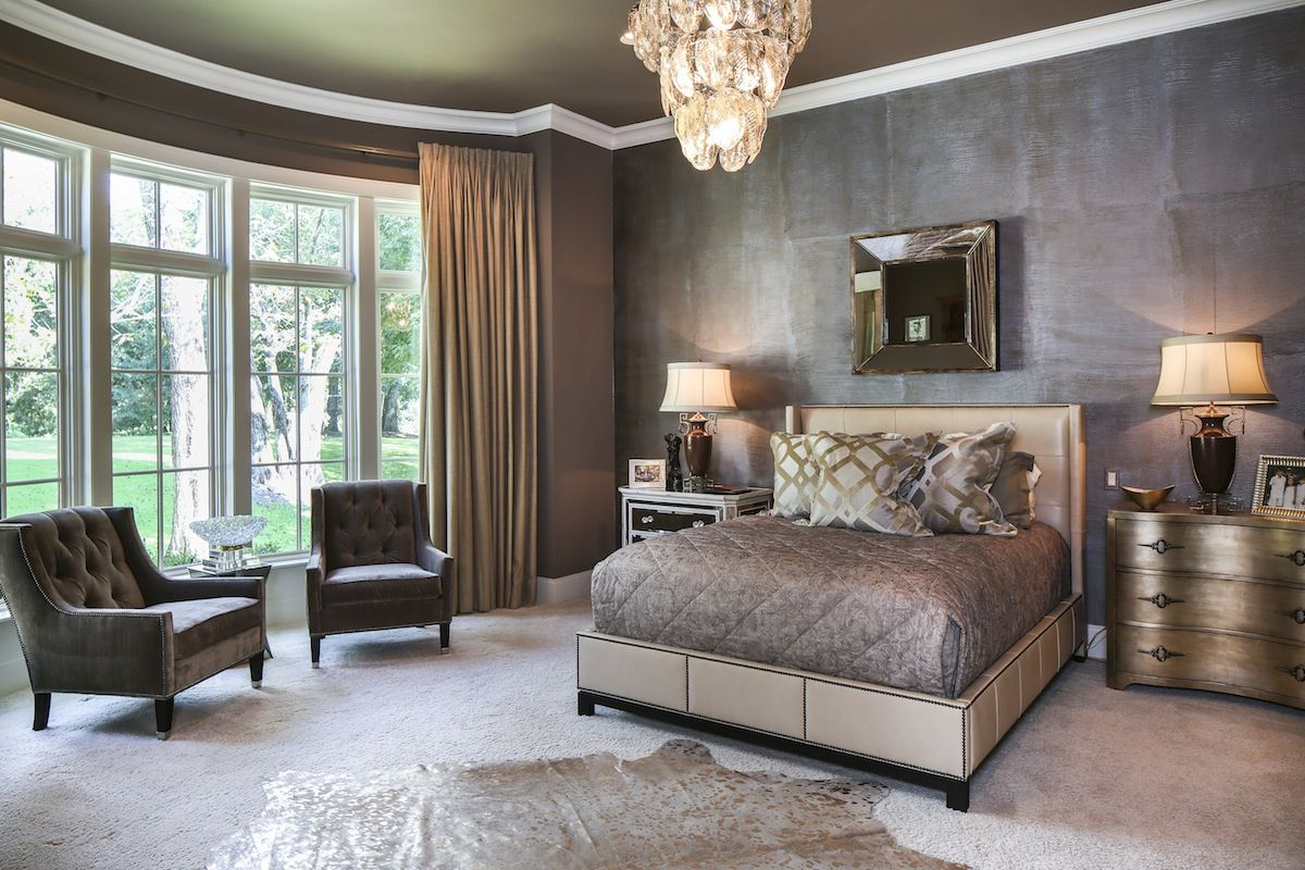 "One wall in the master bedroom features an ""elephant-skin"" textured faux finish created by Connie Perque, and a bowed wall of windows provides a perfect view of the backyard."