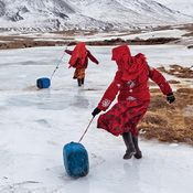 Pictures Of A Place Where No One Should Live #plasticjugs Kyrgyz girls slide plastic jugs back to their family's camp after chopping a hole in a frozen spring to fetch water. Men handle herding and trading; much of the hard labor of daily life falls to the females. #plasticjugs