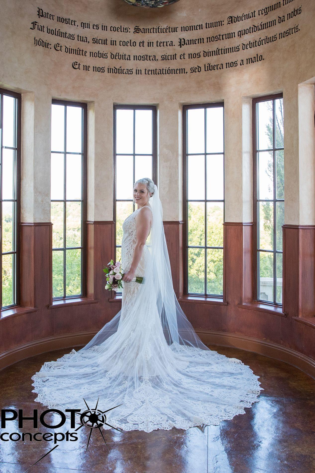 Beautiful bride in rotunda with Latin script writing at ...