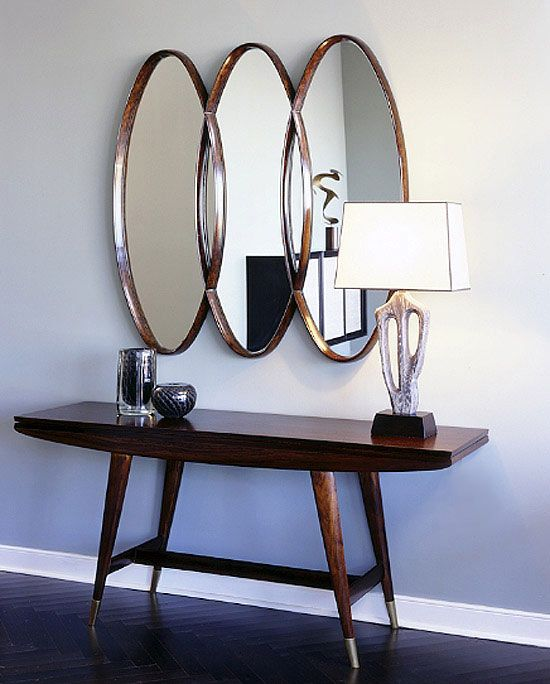 Foyer: Mid-century modern vibe. Love the oval mirror and herringbone wood floor.
