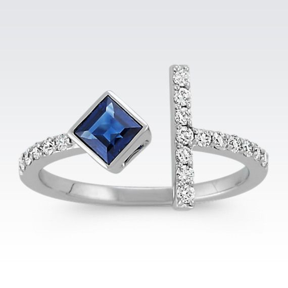 This unique, open style fashion ring exudes creativity and makes a bold statement with one princess cut traditional blue sapphire adding bold color (approx. .35 carat).  The vertical bar and side edges of this ring hold 18 round diamonds (approx. .26 carat TW) adding immense sparkle.  The total gem weight of this fashion forward style is approximately .61 carat.