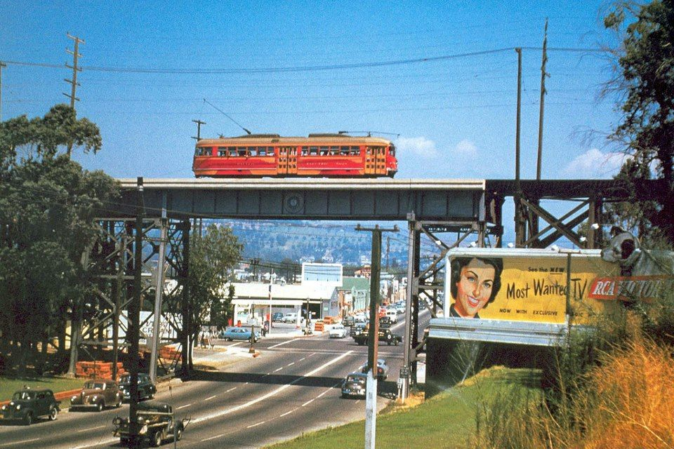 A Pacific Electric red car atop a steel bridge above