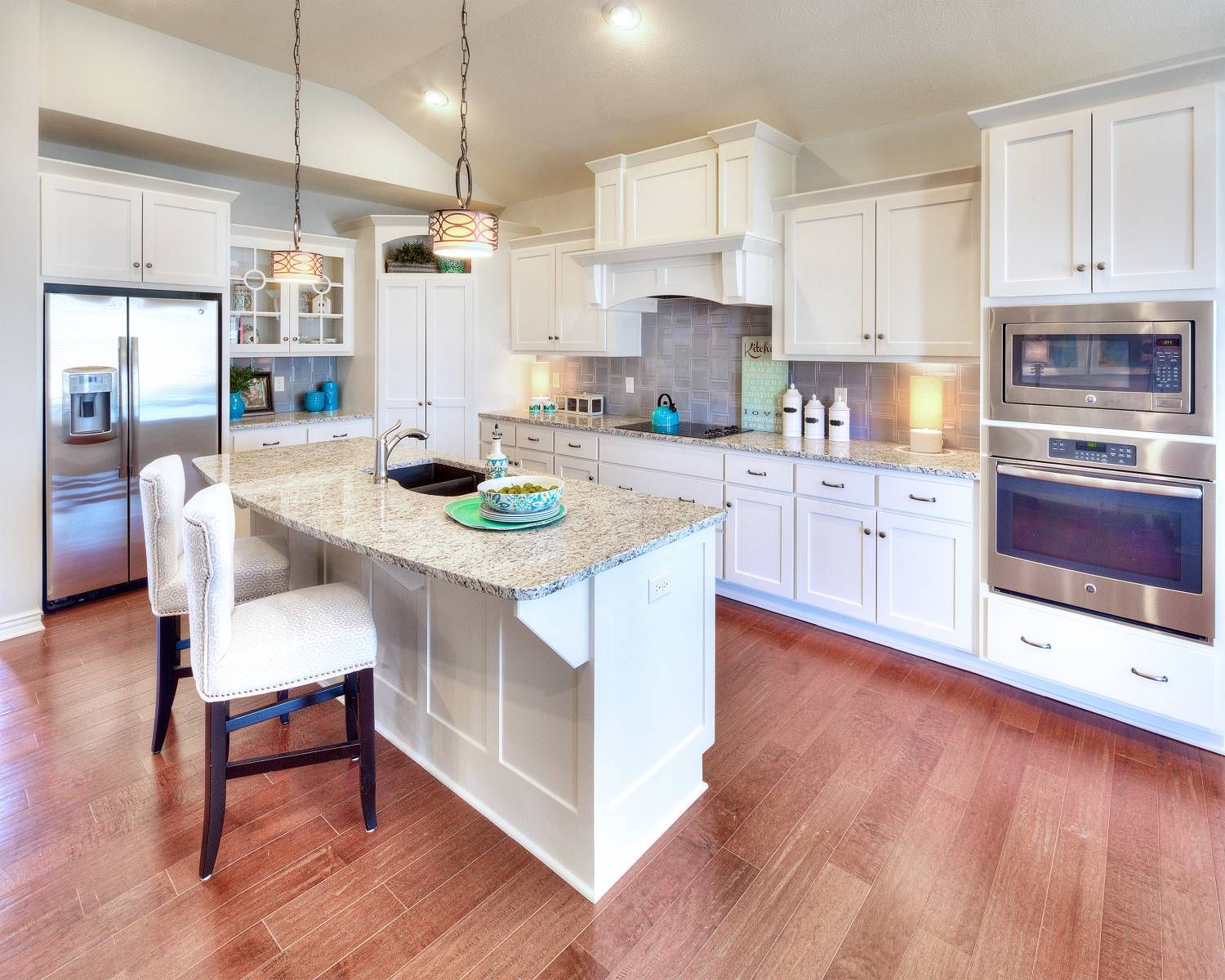 White cabinetry, light wood floor and stainless steel appliances in ...