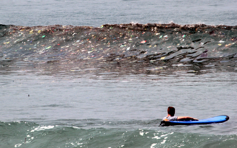 A Surfer Gets Ready To Plow Through A Wave Of Trash At Kuta Beach