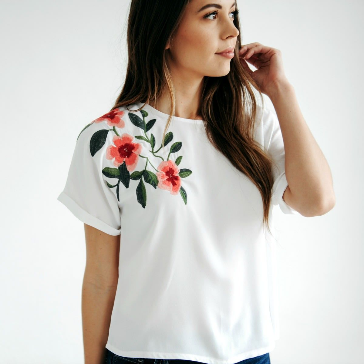 We love this over the shoulder embroidered top! It is a perfect transitional piece for spring and summer. Features a longer rolled sleeve, beautiful embroidered shoulder, and shorter hemline.