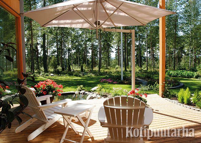 Tältä terassilta aukeaa upea metsämaisema. Aurinkovarjo antaa sopivasti suojaa.
