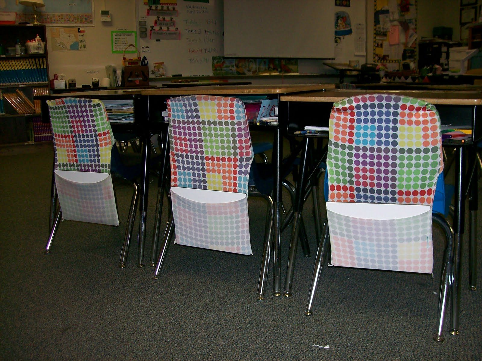 So smart!  Use stretchable book covers as chair pockets.  You can stock up during back-to-school sales!