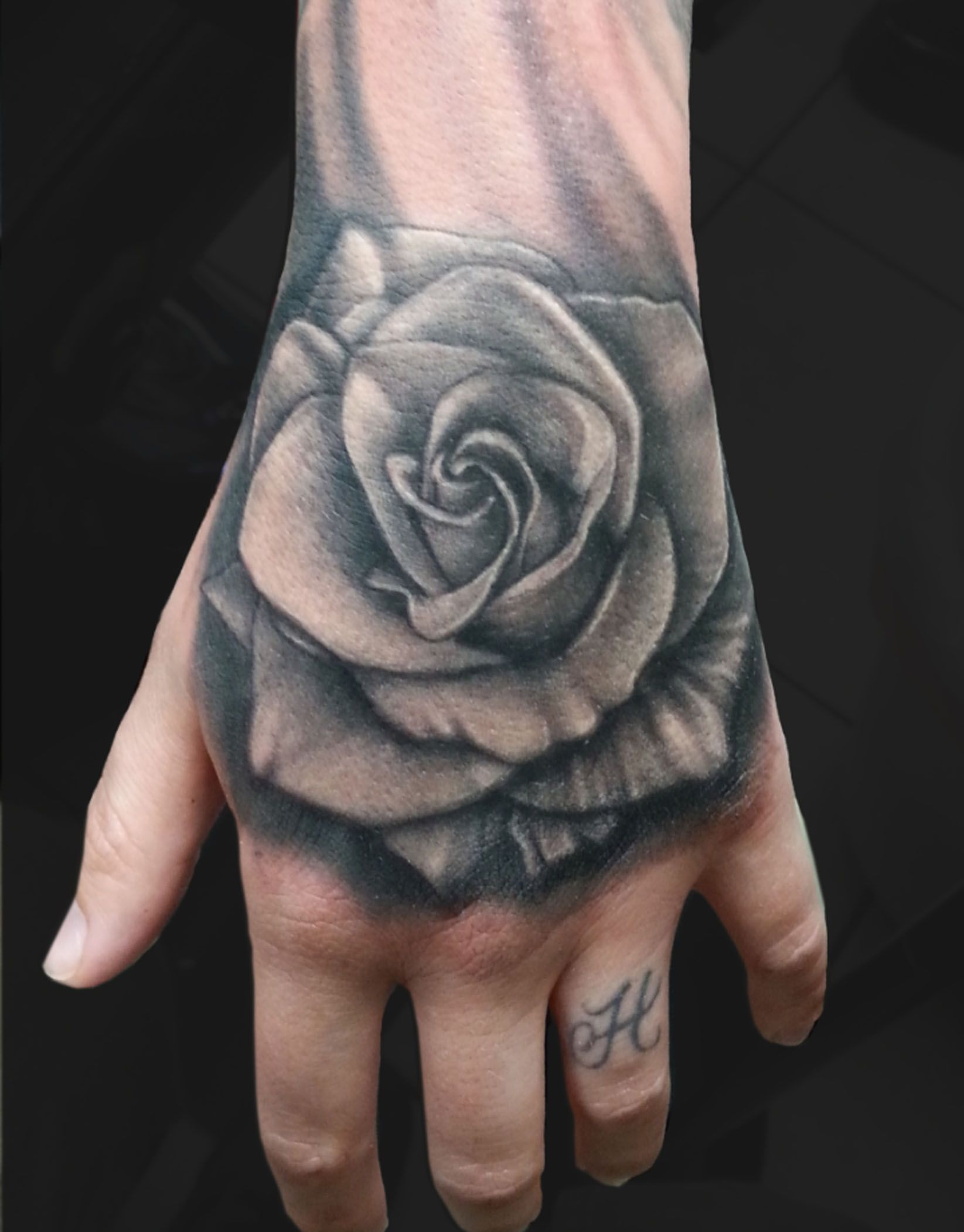Black and grey rose hand tattoo by jesse vardaro at fable