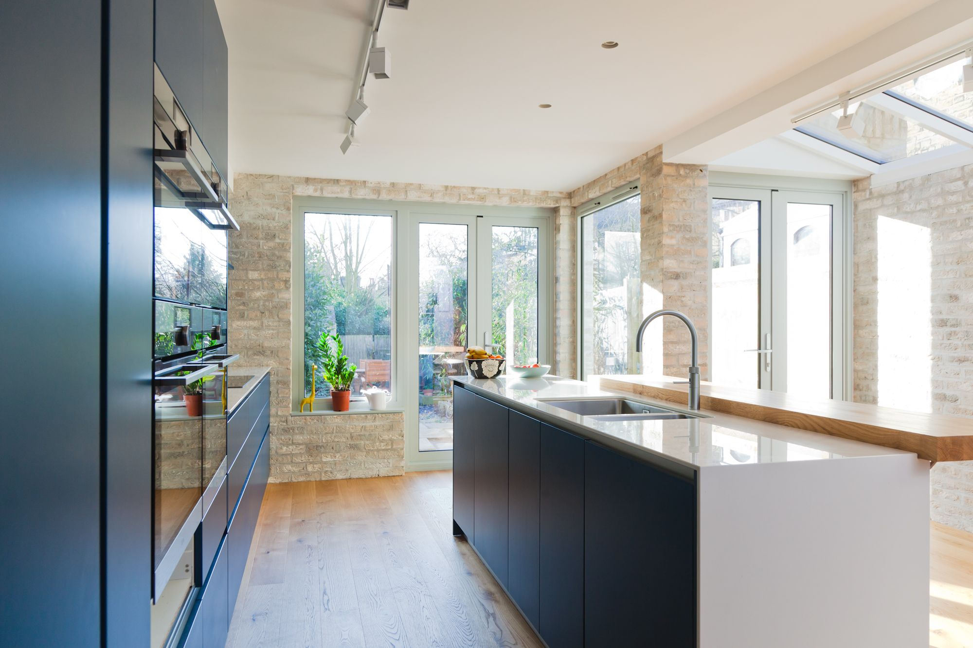 Contemporary, light kitchen. Puccini Kitchens. Exposed brick wall ...