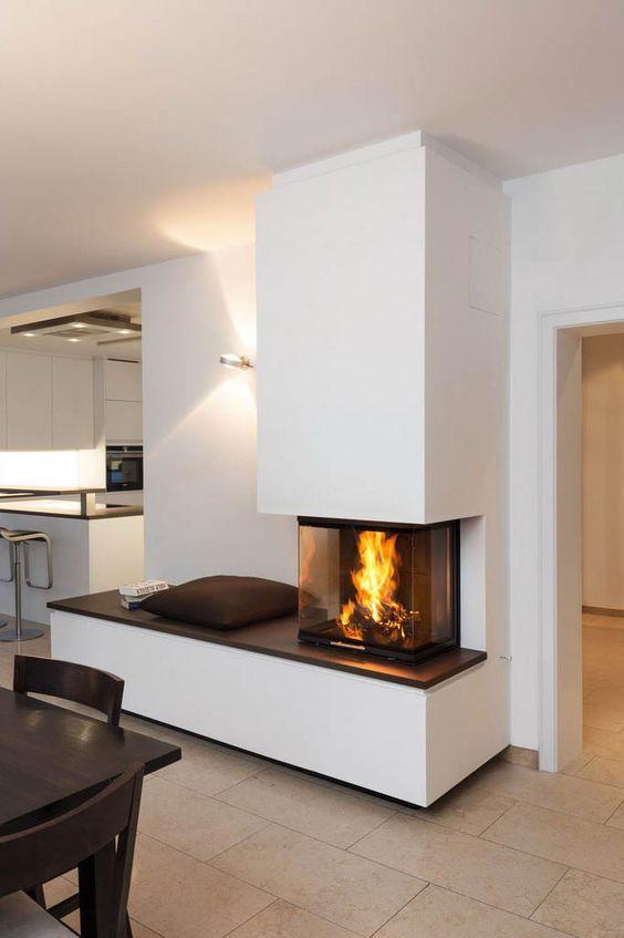 ein dreiseitiger mit glasscheibe geschlossener kamin mit angrenzender sitzbank die. Black Bedroom Furniture Sets. Home Design Ideas