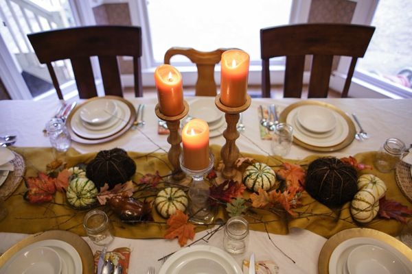 Traditonal Harvest Thanksgiving Table With Gold Runner. Pillar Candles,  Leaves, Pumpkins, Sticks