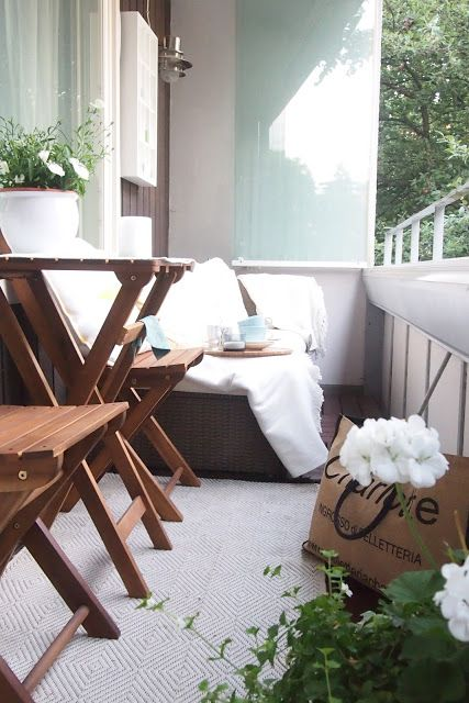 Balcony of a Helsinki apartment with dark wood furniture, white textiles and white geraniums.