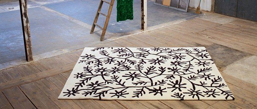 Alfombra Flores. Colección Black on White de Nani Marquina. Tomando como referente un cuadro de Picasso, la diseñadora Sybilla llena de flores de trazos esenciales la superficie blanca. Tallos, pétalos y demás ramificaciones, en negro, se entrelazan formando un tapiz elemental. En la línea del arte abstracto, las alfombras Flores implican un pulso entre feminidad y dureza, imprecisión y simplicidad. Son realizadas mediante la técnica Hand tufted.
