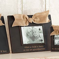 """Wood frame with burlap bow and """"when a child is born so too are grandparents"""" etched below photo opening. Holds 5"""" x 7"""" photo.  $34.00"""