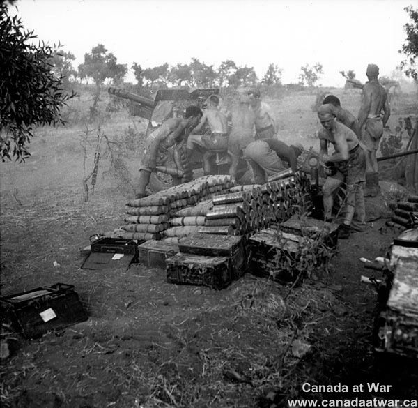 Sicily - Amid heat and dust, gunners of the 7th Battery, 2nd Field Artillery Regiment firing at enemy positions with a 25-pounder gun, Nissoria, July 28th, 1943.