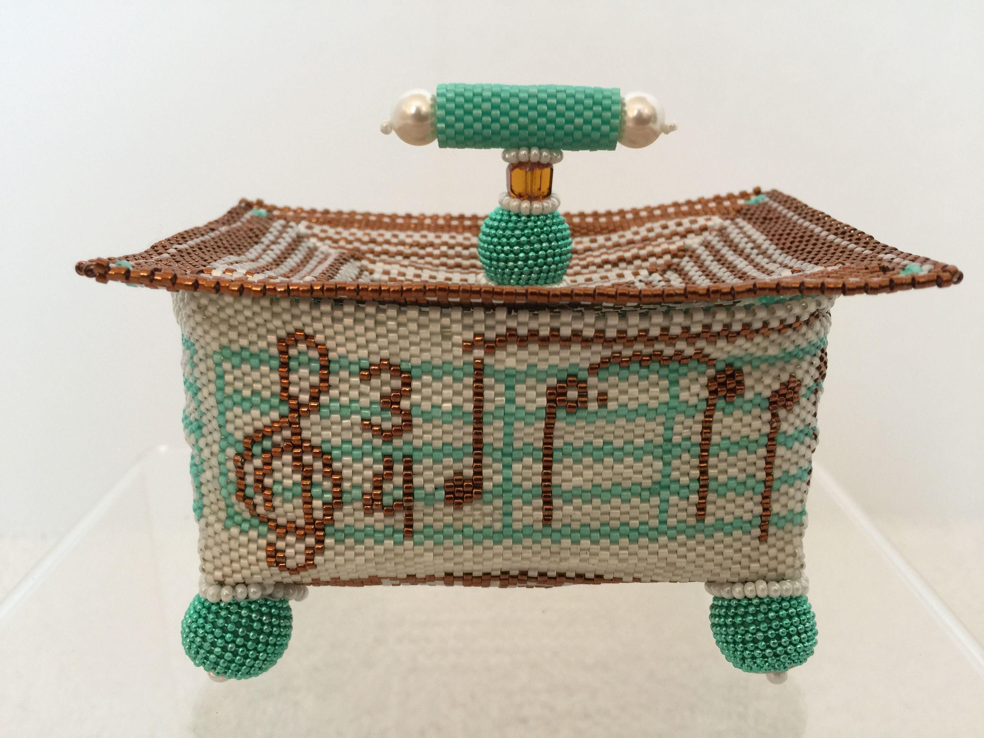 """Music Box"", 2016.  The box is based on a pattern by Julia Pretl.  I used an original color palate, significantly modified the lid, and created an original handle design.  Beaded boxes are entirely made of fishing line (thread) and small seed beads.  The box measures 2.25"" by 3.25"" not including the feet or the handle."