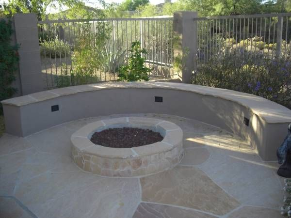A formal mortared flagstone firepit area. The rounded bench seating accents the firepit. The plants behind the bench complete the corner of the yard by softening it up.