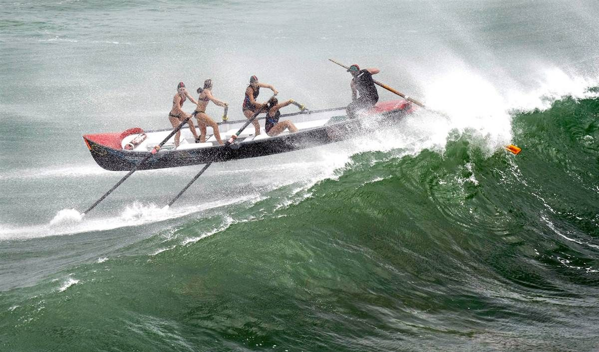 The Piha women's surf boat crew rides up and over a big