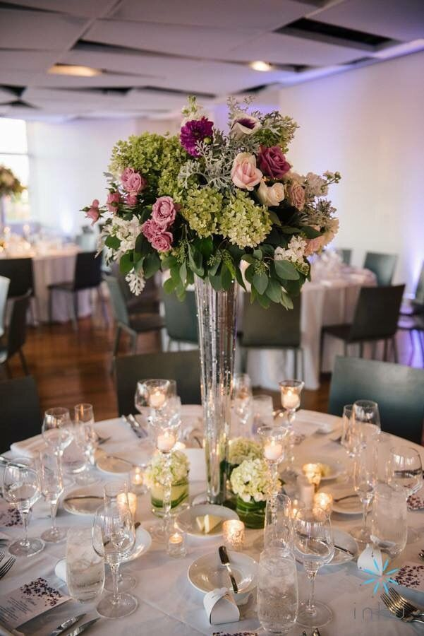 A tall centerpiece with green, purple, pink and white flowers in a mercury holder with clusters of candles is the perfect inspiration for a romantic and modern wedding in the spring