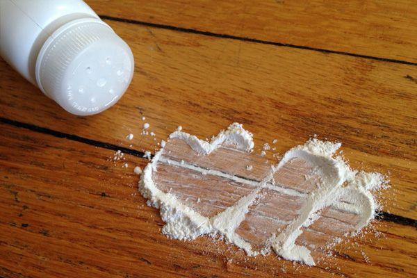 Fixing a squeaky wood floor by sprinkling talc powder between floorboards // maintenance, home hacks //