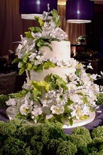 A modest white cake is dressed up with the addition of white sugar flowers and leaves.