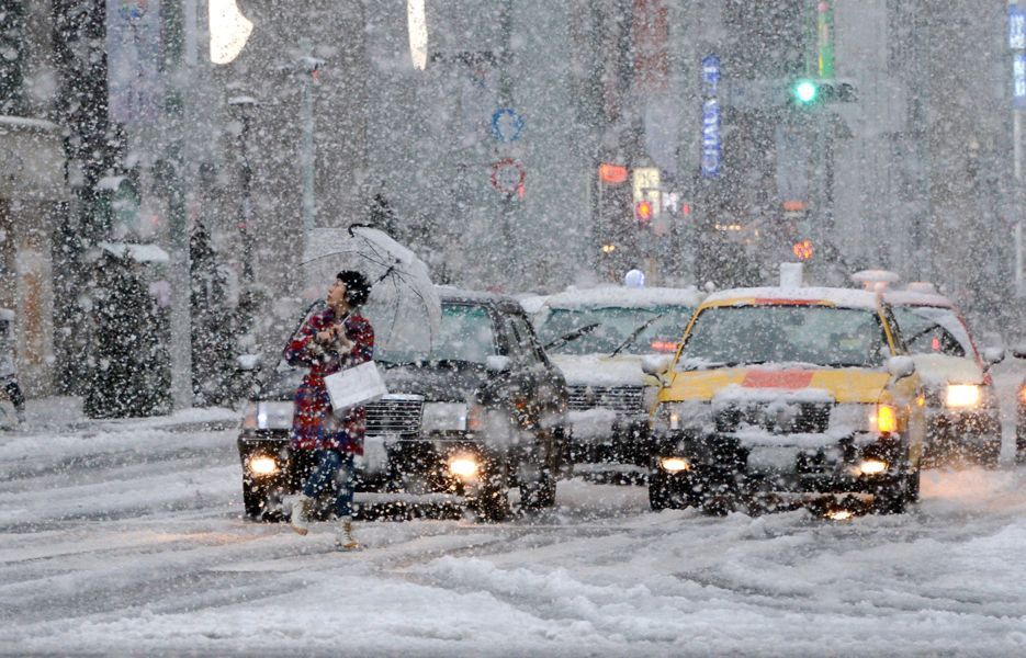 A pedestrian looks at the falling snow while crossing the road in the Ginza shopping district in Tokyo on Jan. 14.
