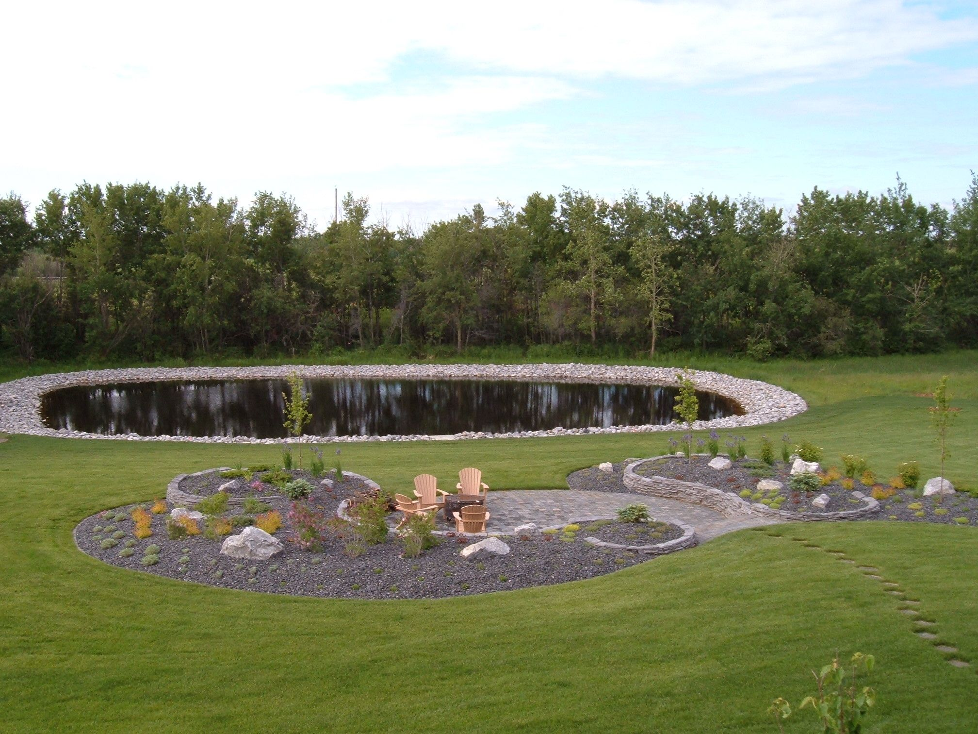 Patio in a hill over looking a pond outlined with for Rock ponds designs