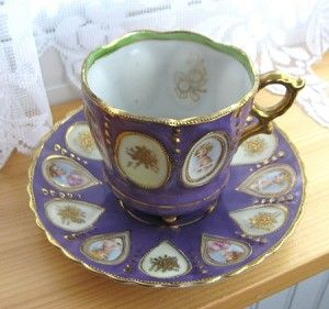 This is an absolutely fabulous Occupied Japan three footed cup and saucer in an unusual bright purple color made by Saji, Japan made in 1945-1952. The design is really incredible with vignettes with raised gold beaded frames of lovely ladies alternating with embossed gold flower vignettes and further gold beaded trim.