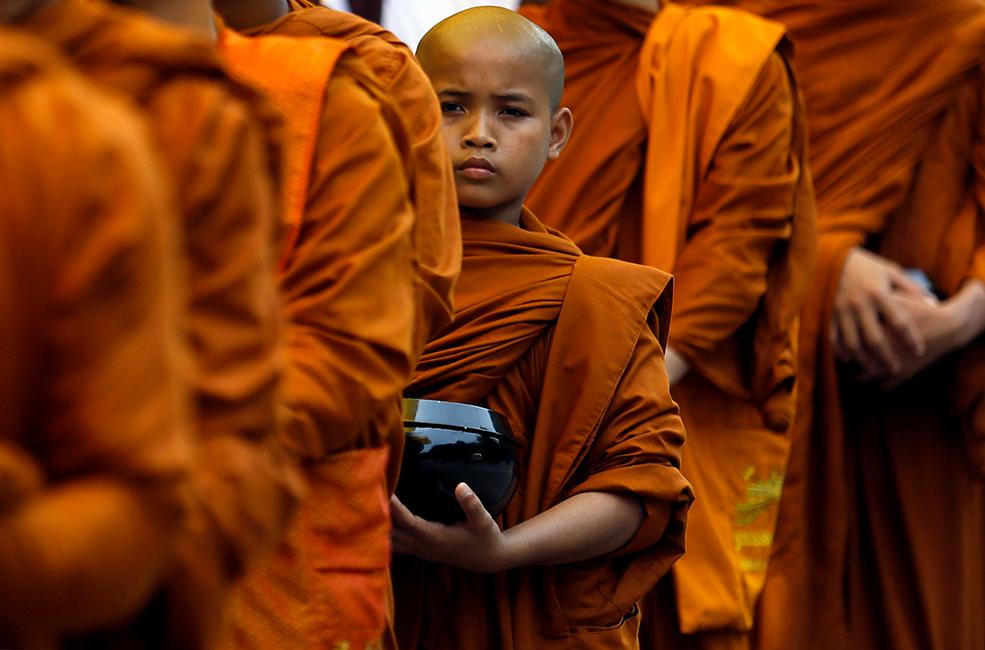 Buddhist monks walk down a road asking for alms during the annual Vesak festival, in Colombo, Sri Lanka.