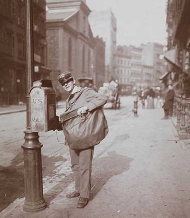 """A letter carrier standing in front of a mailbox at Mott Street above Park Row,"" 1903. (Courtesy of the MCNY)"