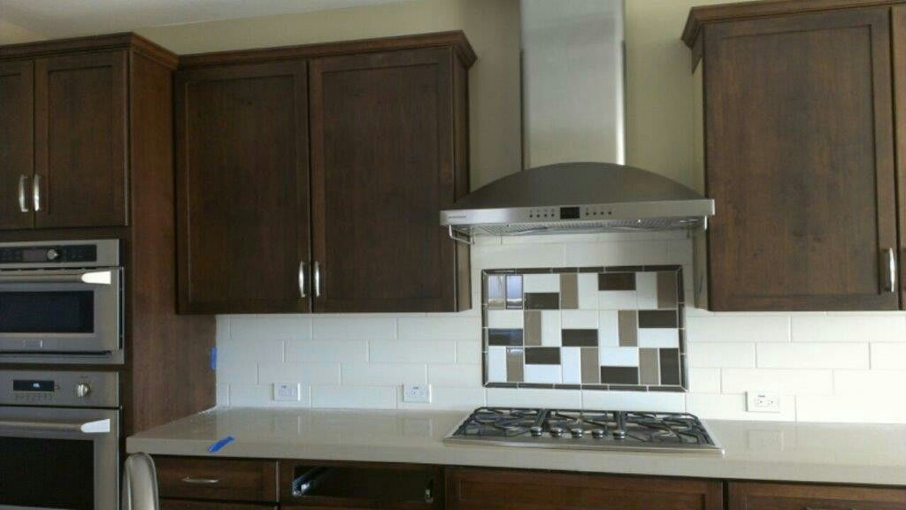 PebbleCreek Community home - Nelson: Cape Cod styled cabinets with Walnut stain. Subway tile backsplash with mosaic above cooktop of trip-color subways in random pattern. GE Monogram Pro Series appliances