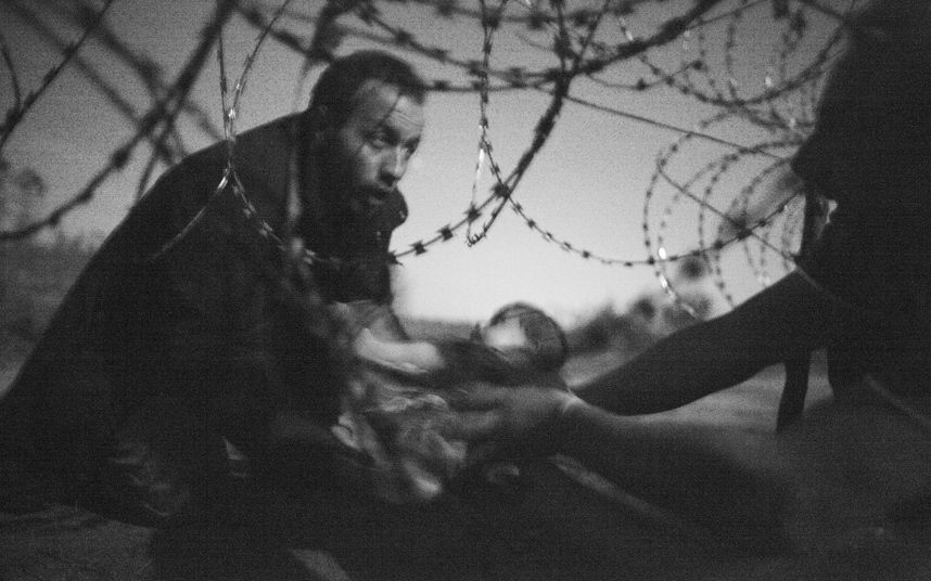A photograph by Australian photographer Warren Richardson has won the World Press Photo of the Year award. The picture shows a man passing a baby through a fence at the Serbia/Hungary border in Roeszke, Hungary on 28 August 2015.