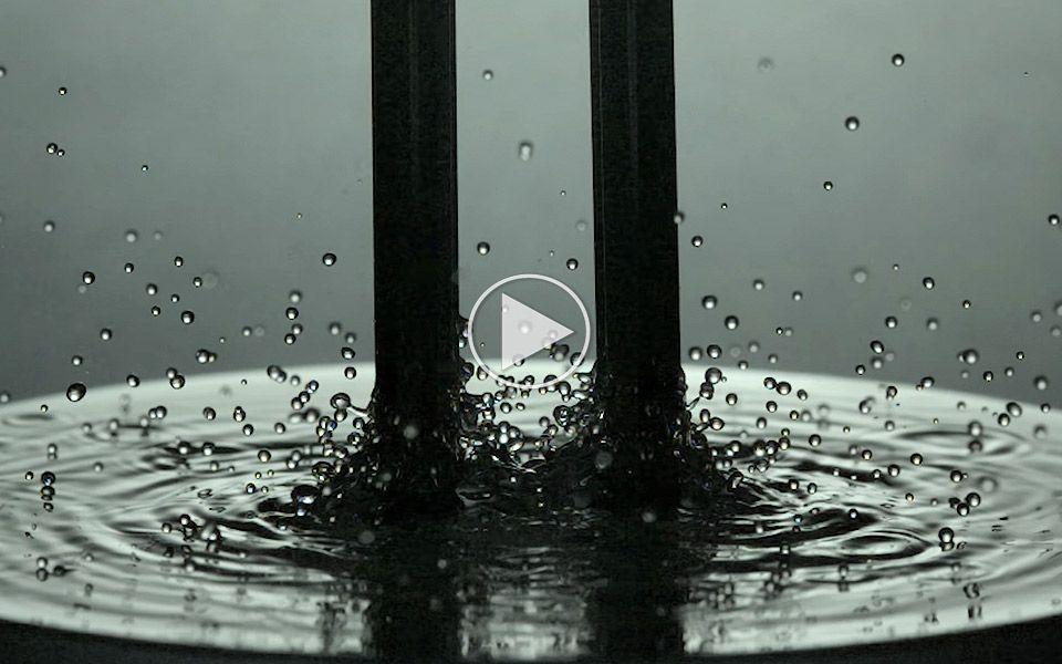 En stemmegaffel i vand filmet i slow motion er hypnotiserende at se på