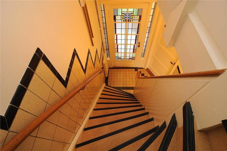 Tegels langs de trap en glas in lood deur te zien in deze jaren 30