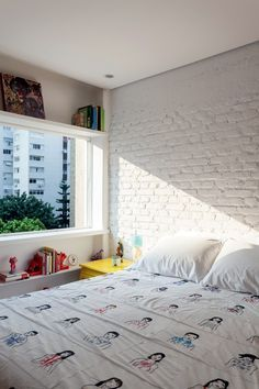 Quarto | Sem o reboco, a parede da cabeceira tem tijolos à vista pintados de branco. Os espaços acima e abaixo da janela receberam prateleiras. Criado-mudo da Estúdio Glória (Foto: Fran Parente)