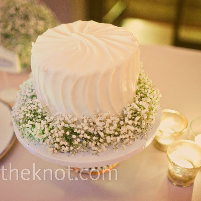A simple garland of baby\'s breath surrounded the small cutting cake ...