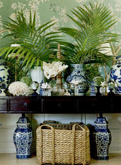 A dark mahogany console covered with a collection of coral, shells, blue & white porcelain, & palm fronds, along with the woven abaca basket and more b&w underneath leave no mistake that one is in the Islands.