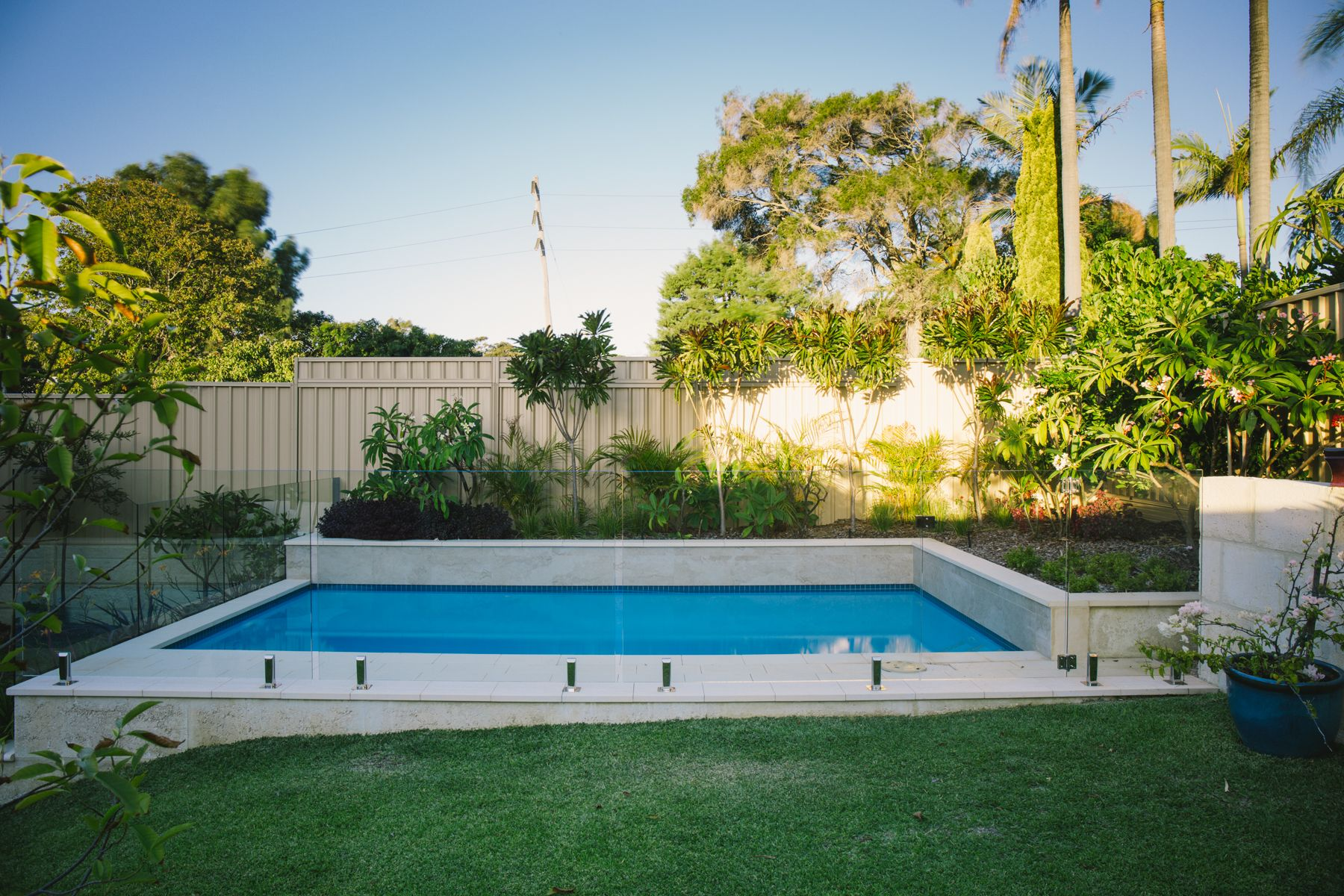 Concrete Pool Installed On A Sloped Backyard Tropical Landscaping To Accompany The Light Blue Pool Colour Pool Landscaping Pool Spa Pool