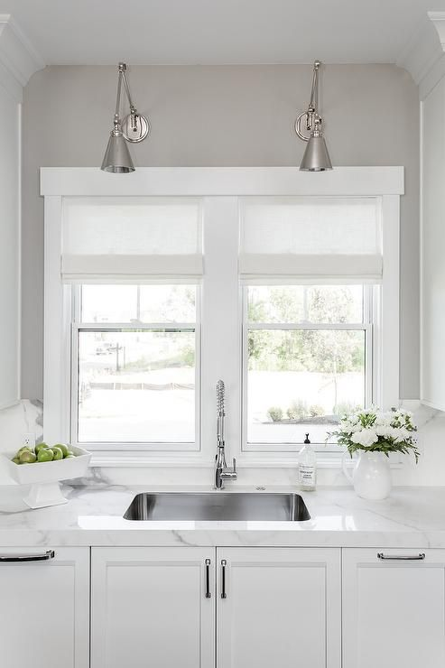 Polished Nickel Swing Arm Sconces Over Curved KItchen Sink