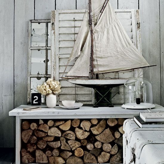 Aged white table, with toy sail boat, modern bulb light against Shaker-style wood fence with driftwood and old chest.