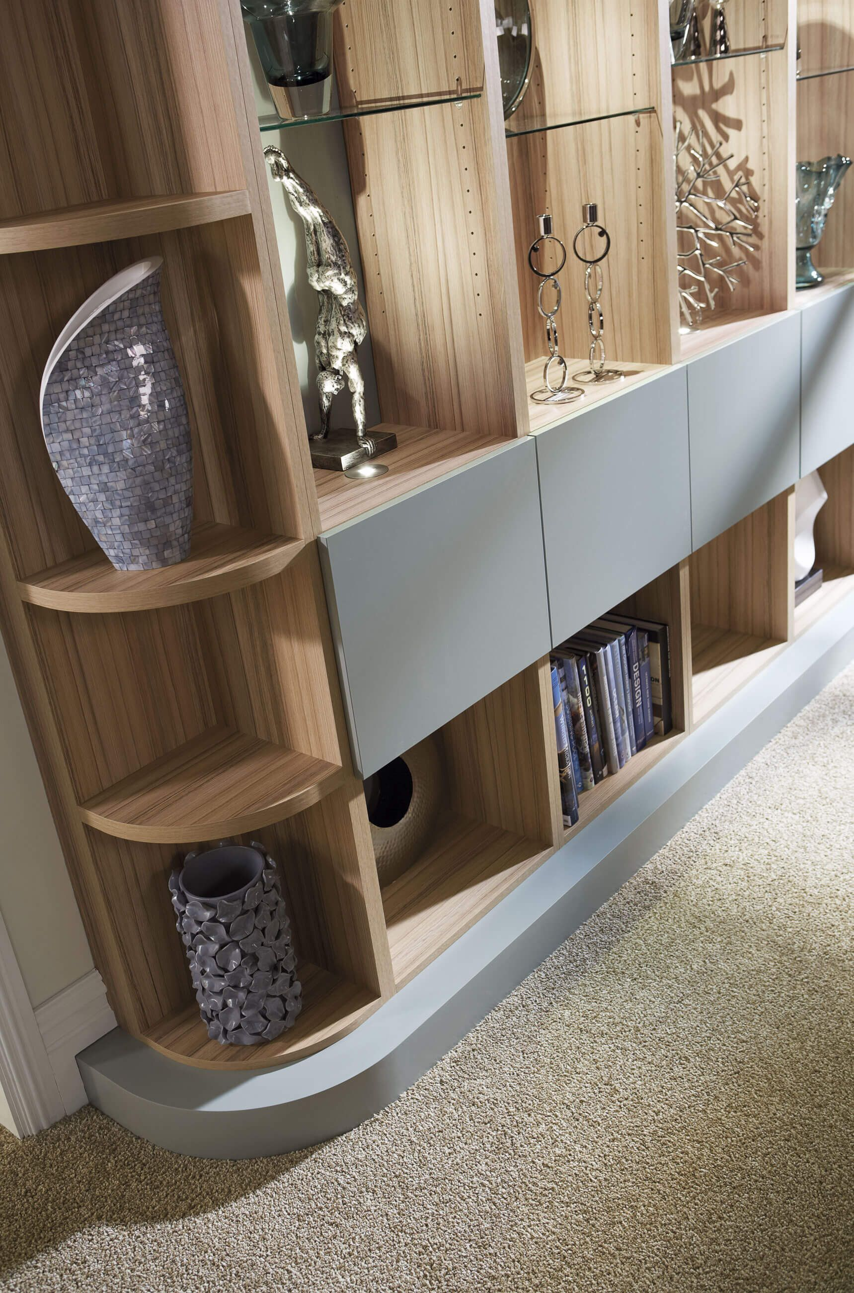 This grey modern library study has curved edges to fit with the flow of the room special features include a coordinating ladder and curved worktops