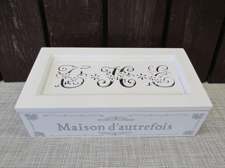 Puinen laatikko kolmella sisälokerolla. Kannessa reikä kuvioitu teksti: THE.