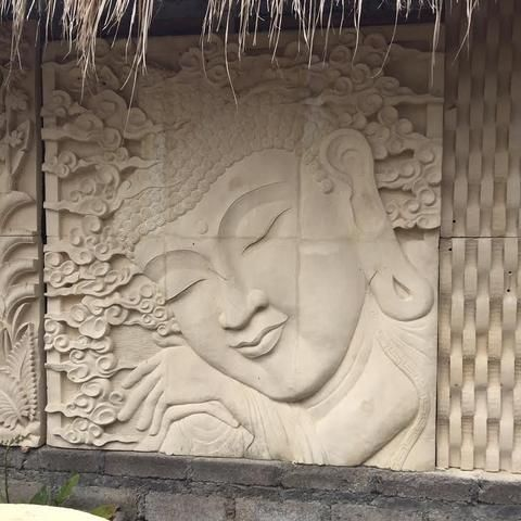 Balinese art stone wall relief of buddha fountain in
