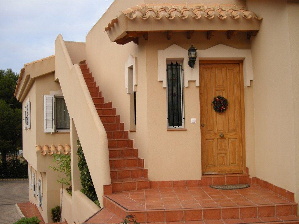 puerta principal de entrada a la vivienda a su izquierda las escaleras de acceso